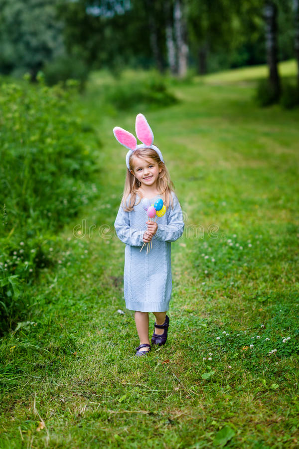 Lächelndes kleines Mädchen mit den langen tragenden Hasenohren des blonden Haares lizenzfreie stockfotografie