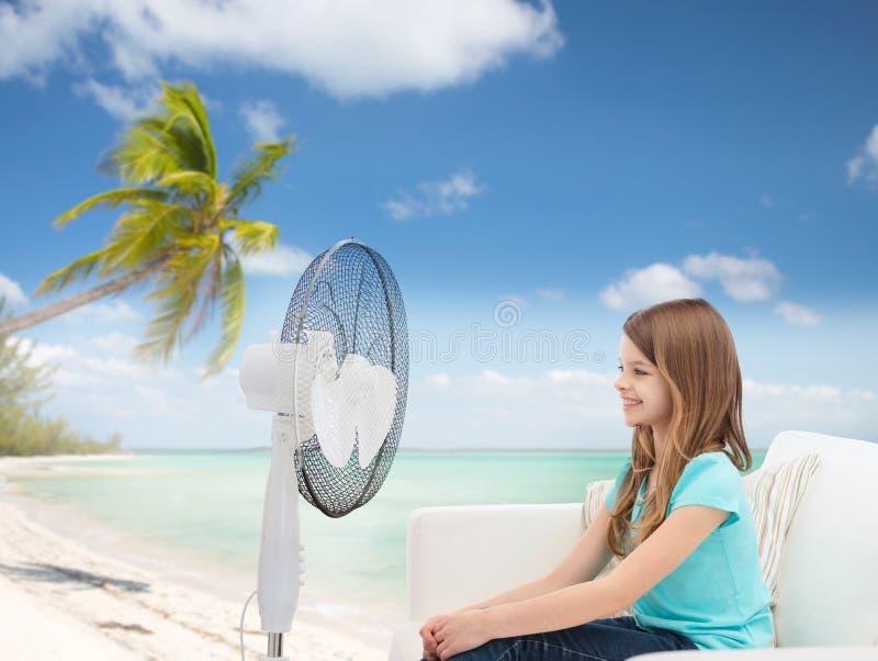 Lächelndes kleines Mädchen mit großem Fan zu Hause lizenzfreie stockfotografie