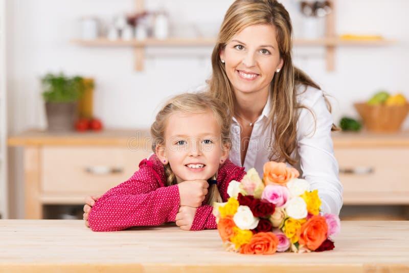 Lächelndes kleines Mädchen mit ihrer Mutter und Blumen stockfotografie