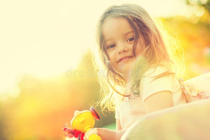 Lächelndes kleines Mädchen mit Spielzeug in den Händen stockbild