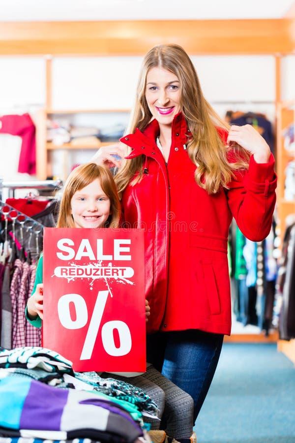 Lächelndes kleines Mädchen und Frau, die Verkaufsangebot fördern stockfotografie