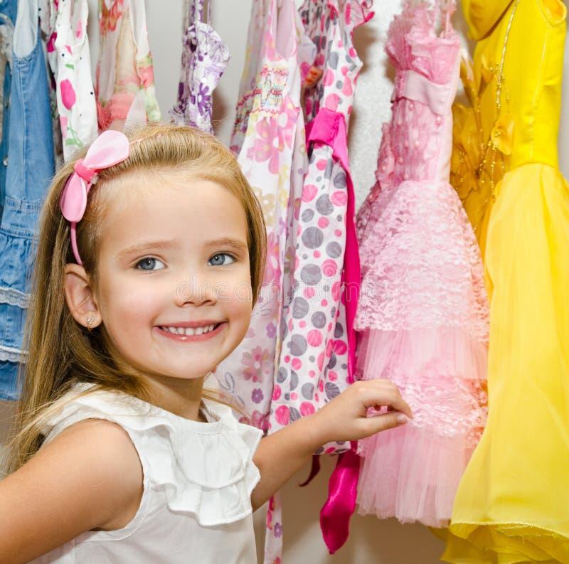 Lächelndes kleines Mädchen wählt ein Kleid von der Garderobe stockfotografie