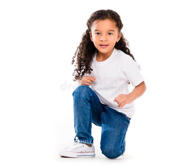 Lächelndes kleines nettes Mädchen knelted auf einem Knie lizenzfreies stockfoto