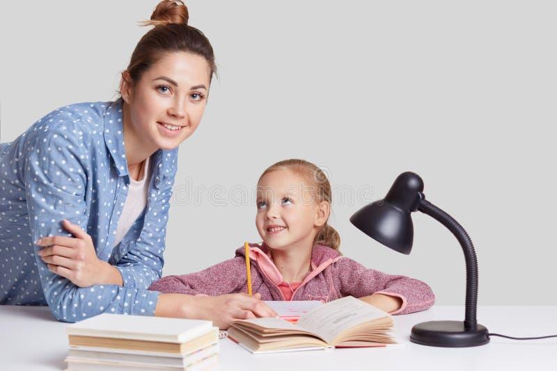 Lächelndes kleines reizend Mädchen sitzt bei Tisch, tut Hausarbeitaufgabe zusammen mit ihrer Mutter, versuchen, Zusammensetzung z lizenzfreies stockbild