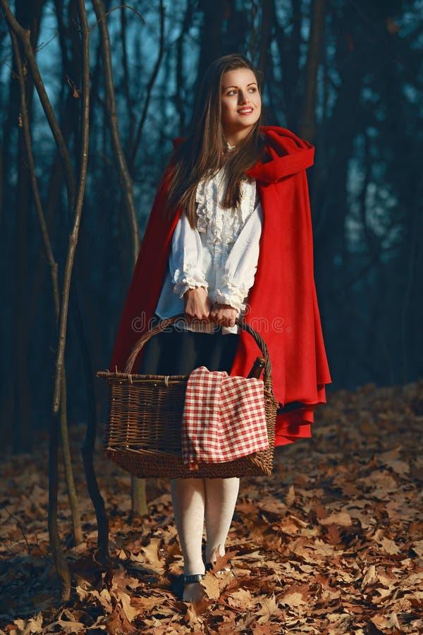 Lächelndes kleines Rotkäppchen im Wald nachts stockbild