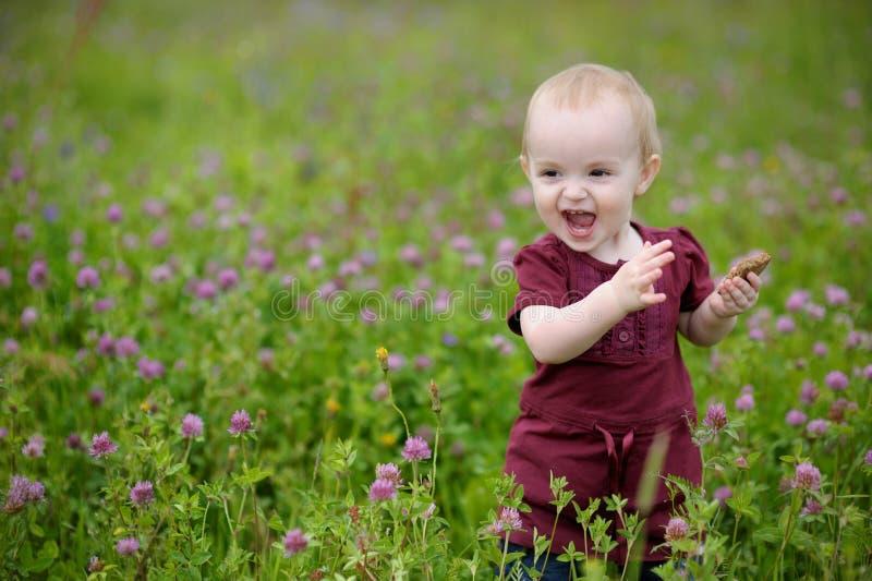 Lächelndes kleines Schätzchen in einer Wiese lizenzfreie stockfotos