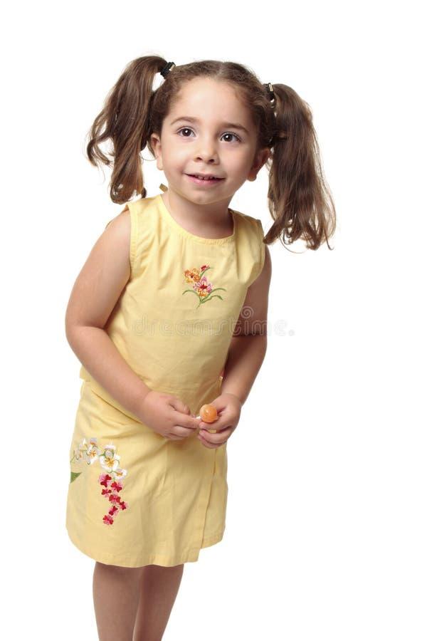 Lächelndes Kleinkind, das eine Süßigkeit anhält stockfoto