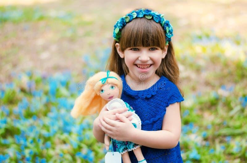 Lächelndes Kleinkindmädchen mit einer Puppe in ihren Händen stockfoto