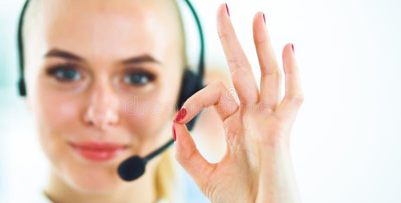 Lächelndes Kundendienstmädchen, das o.k., lokalisiert auf weißem Hintergrund darstellt stockfotografie
