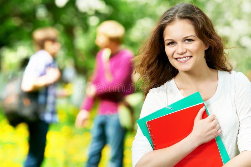 Lächelndes Kursteilnehmermädchen draußen mit Übungsteilen stockfoto