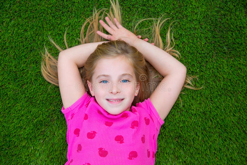 Lächelndes Lügen des schönen blonden Kinderkindermädchens auf Gras stockbilder