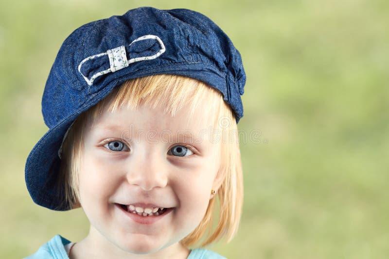 Lächelndes llittle Mädchen mit einer Kappe auf ihrem Kopf auf einem grünen Hintergrund stockbilder