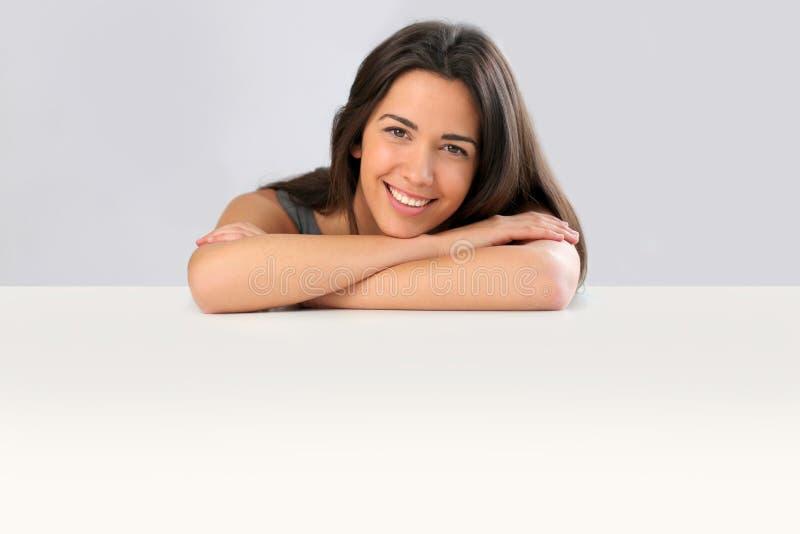 Lächelndes lokalisiertes Lehnen der jungen Frau auf Tabelle lizenzfreie stockbilder