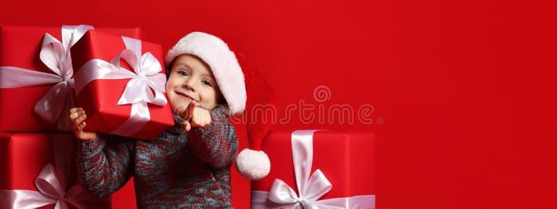 Lächelndes lustiges Kind in rotem Hut Sankt, der in der Hand Weihnachtsgeschenk hält Weihnachtsniederlassung und -glocken lizenzfreie stockbilder