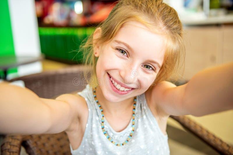 Lächelndes lustiges kleines Mädchen, das selfie tut stockfoto