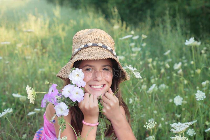 Lächelndes Mädchen auf dem Blumengebiet stockbild