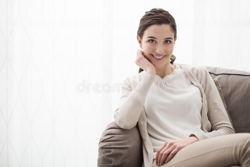 Lächelndes Mädchen auf der Couch stockfotos