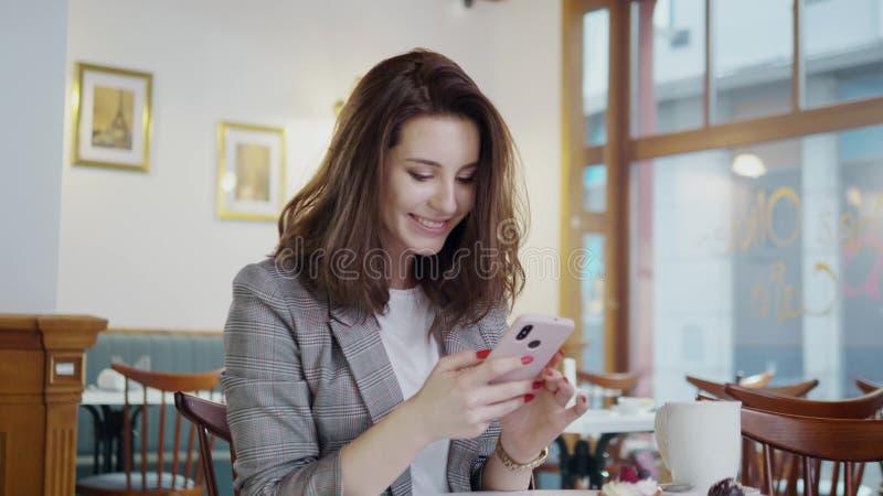 Lächelndes Mädchen Beaufitul mit Handy in einem Café lizenzfreie stockbilder