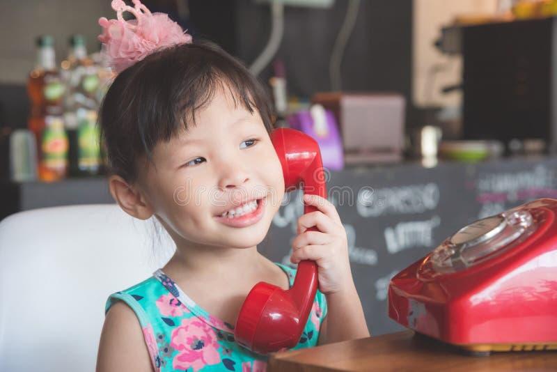 Lächelndes Mädchen bei der Unterhaltung mit ihrem Freund durch rotes klassisches Telefon stockfoto