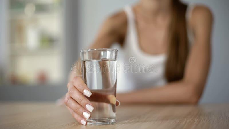 Lächelndes Mädchen bietet Glas Wasser, hält Körper hydratisierte, befeuchtete Haut an lizenzfreie stockbilder