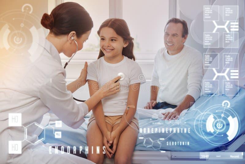 Lächelndes Mädchen, das auf dem Bett während ein Doktor überprüft sie mit einem Stethoskop sitzt lizenzfreies stockbild