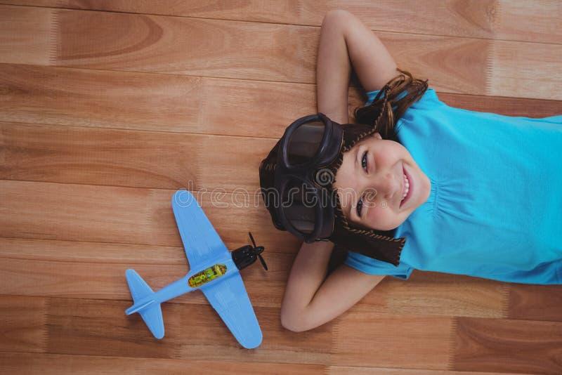 Lächelndes Mädchen, das auf die tragenden Fliegergläser und -hut des Bodens legt stockbild
