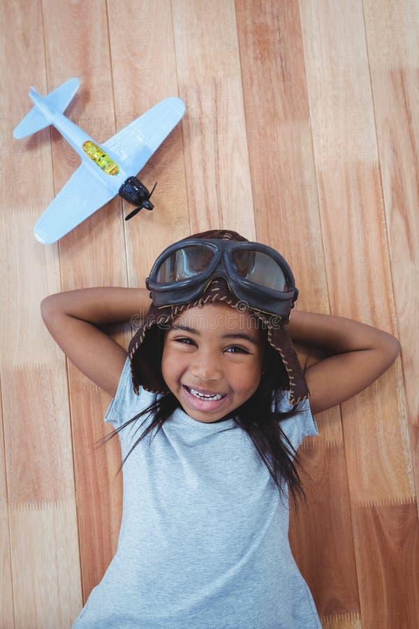 Lächelndes Mädchen, das auf die tragenden Fliegergläser und -hut des Bodens legt lizenzfreie stockbilder