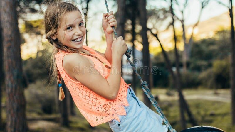 Lächelndes Mädchen, das auf einem Reifenschwingen in einem Park spielt lizenzfreies stockfoto
