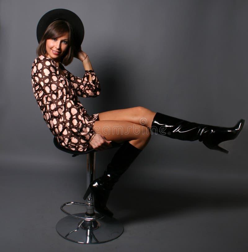 Lächelndes Mädchen, das auf einem Stuhl sitzt lizenzfreie stockfotos