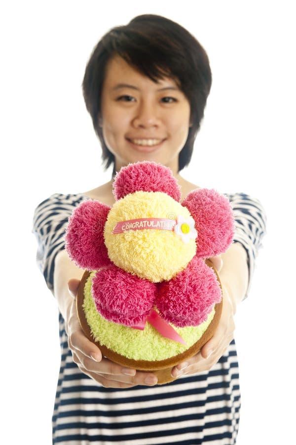 Lächelndes Mädchen, das Blume gibt lizenzfreies stockfoto