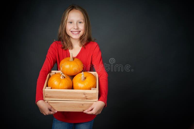 Lächelndes Mädchen, das einen Kasten mit orange Kürbisen hält stockbild