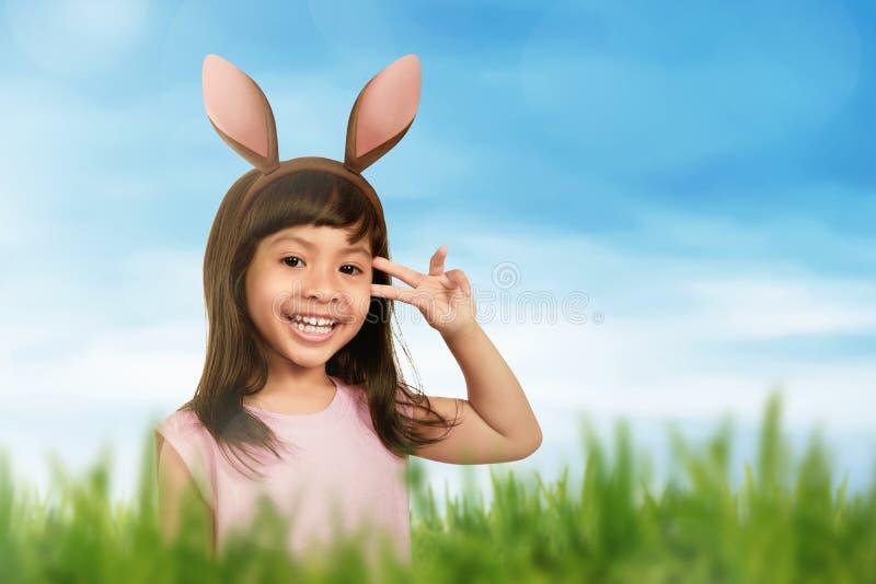 Lächelndes Mädchen, das Häschenohren in ihrem Haar verwendet stockfotos