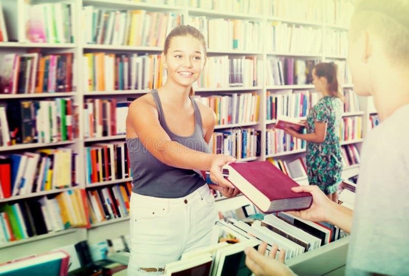 Lächelndes Mädchen, das Hilfe bei der Buchwahl erhält stockbild