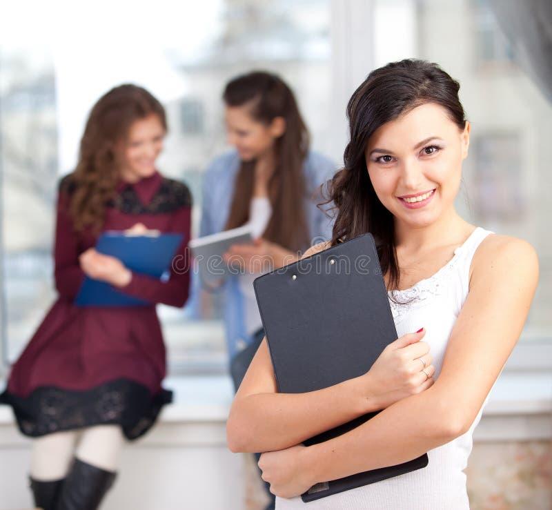 Lächelndes Mädchen, das Kamera im College betrachtet stockfotografie