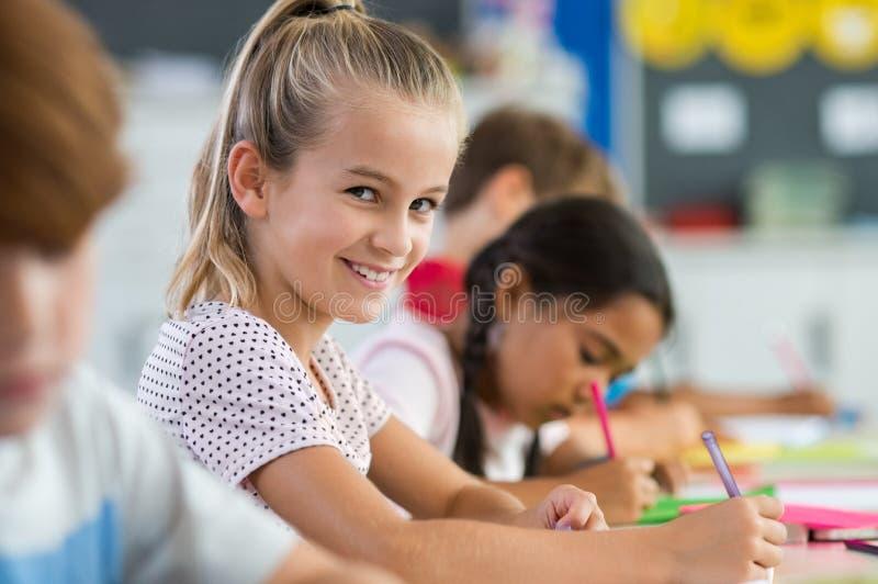 Lächelndes Mädchen, das Klassenarbeit tut stockfotografie