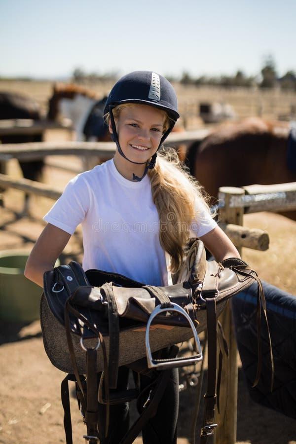Lächelndes Mädchen, das Pferdesattel hält lizenzfreie stockfotos