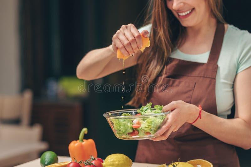 Lächelndes Mädchen, das Salat zubereitet lizenzfreie stockfotos