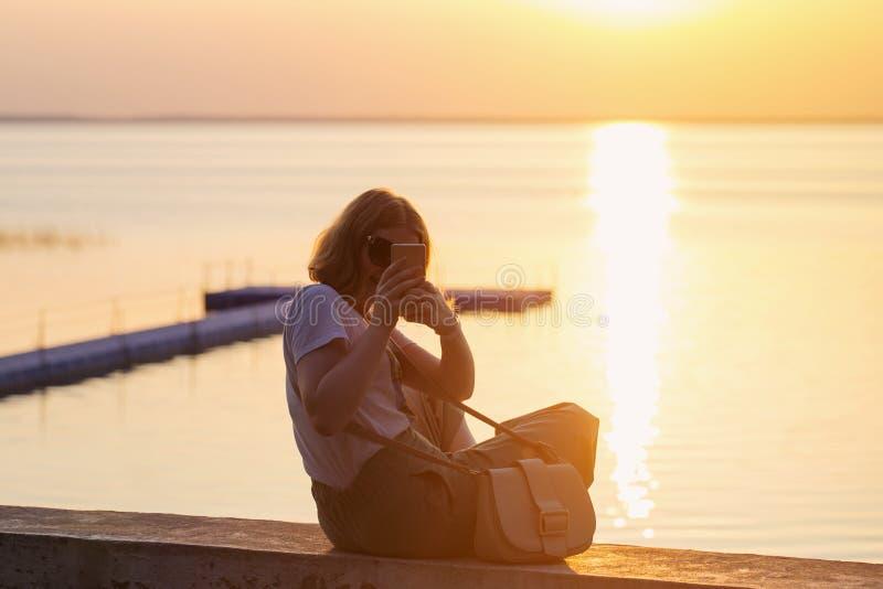 lächelndes Mädchen, das selfie auf Hintergrund des Sonnenuntergangs macht lizenzfreie stockfotos