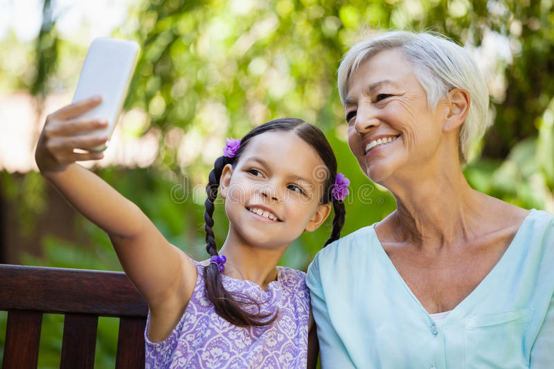 Lächelndes Mädchen, das selfie mit Großmutter nimmt stockbild