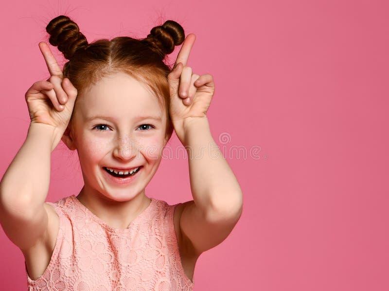 Lächelndes Mädchen, das Spaß und die Herstellung von Hörnern durch ihre Hände hat stockbilder
