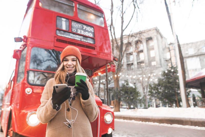 Lächelndes Mädchen in den warmen Kleidungsständen in der Straße an einem Wintertag mit einem Tasse Kaffee und einem Smartphone in stockbild