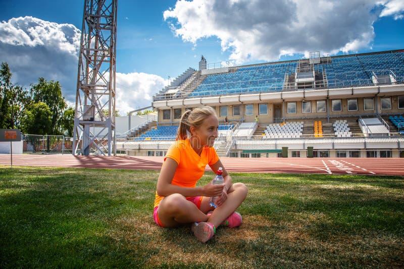 Lächelndes Mädchen in der orange Sportkleidung, die auf Stadion ` s Feld von sitzt stockbild
