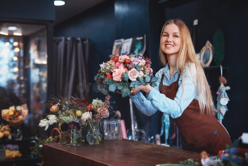 Lächelndes Mädchen in einem Blumenladen lizenzfreies stockbild