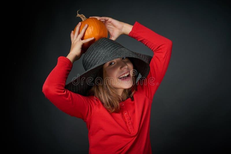 Lächelndes Mädchen in einem schwarzen Hut, der orange Kürbis hält stockfoto