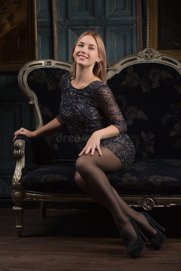 Lächelndes Mädchen in einem schwarzen Kleid in einem Luxusraum lizenzfreie stockfotografie