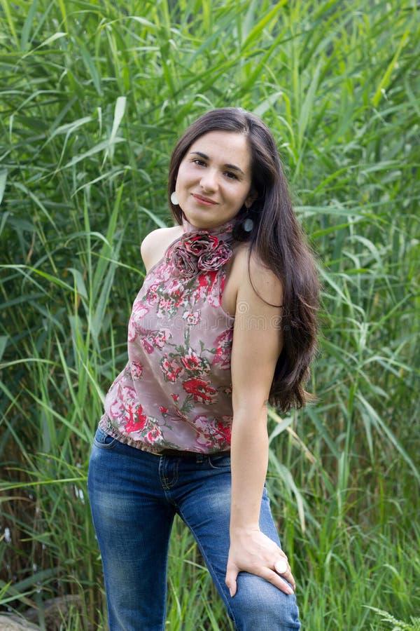 Lächelndes Mädchen gegen einen grünen Stock stockbild