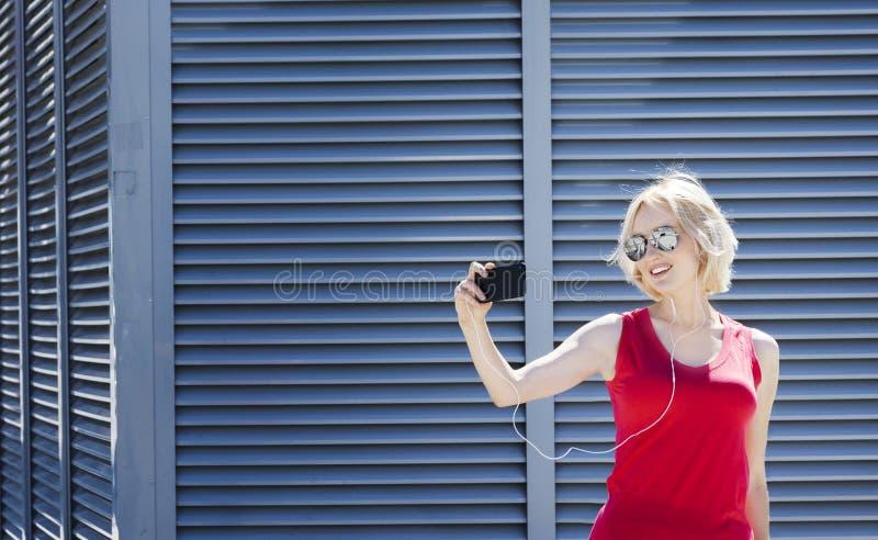 Lächelndes Mädchen im roten Hemd, das ein Foto auf Smartphone, gegen Metall macht, streifte Hintergrund Tag, im Freien lizenzfreie stockfotografie
