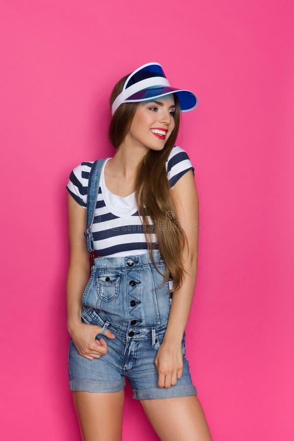 Lächelndes Mädchen in Jean Dungarees Shorts stockfotos