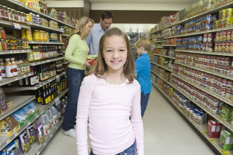 Lächelndes Mädchen mit dem Familien-Einkaufen im Supermarkt lizenzfreie stockfotos