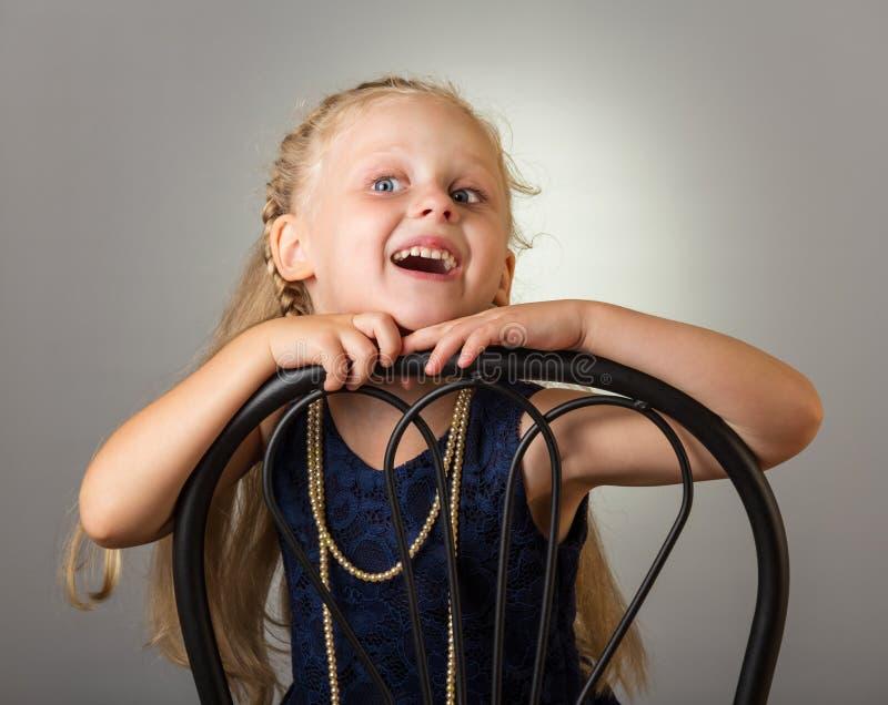 Lächelndes Mädchen mit dem langen Haar im Kleid mit den Perlen, die auf Stuhl, auf Grau sitzen lizenzfreie stockfotografie